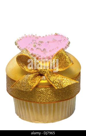 Tasse Kuchen verziert mit goldenen Vereisung und Bogen auch rosa Herz isoliert auf weiss. - Stockfoto