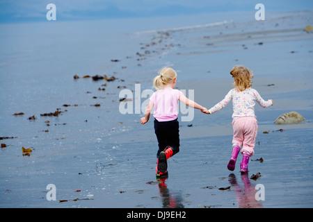 Zwei Mädchen Kleinkinder am Strand Hand in Hand am Ankerpunkt In Yunan Alaska. - Stockfoto