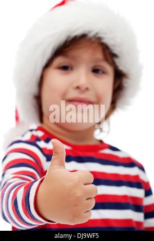 Entzückende kleine Junge Santa Hut und geben Sie Daumen nach oben - Fokus auf Seite - Stockfoto