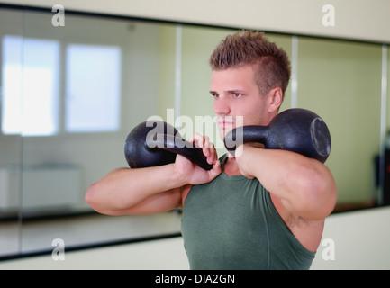 Attraktive junge sportlicher Mann im Fitness-Studio trainieren, trainieren mit kettlebells - Stockfoto