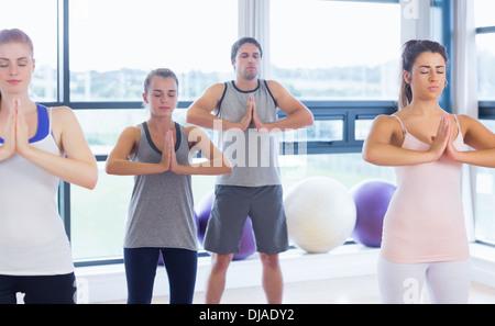 Fitness-Klasse und Lehrer stehen in Namaste position - Stockfoto