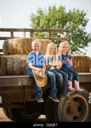 Kaukasische Kinder sitzen auf LKW auf Bauernhof - Stockfoto