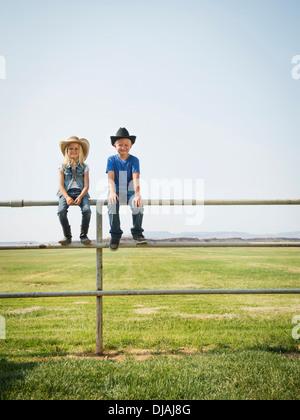 Kaukasische Kinder sitzen auf Zaun auf Bauernhof - Stockfoto