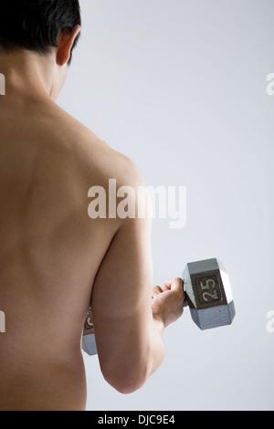 Nackter Oberkörper athletischen Mann tun locken mit freien Gewichten - Stockfoto