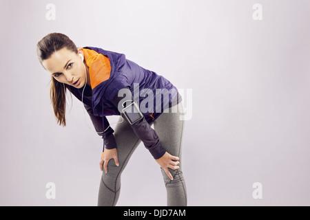 Schöne junge Frau in Sportkleidung auf der Suche müde nach einem Lauf. Weibliche Läufer ruhen mit den Händen auf - Stockfoto