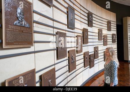 Eine Frau schaut die Plaques gewidmet Country Musikstars an einer Wand in die Country Music Hall Of Fame in Nashville, - Stockfoto