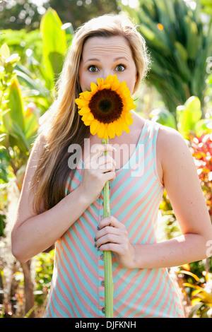 Porträt eines Mädchens, die Augen weit mit einer Sonnenblume vor den Mund; Honolulu, Oahu, Hawaii, Vereinigte Staaten - Stockfoto