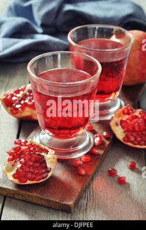 Reife Granatapfel-Frucht und ein Glas Saft auf hölzernen Hintergrund - Stockfoto