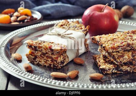 Müsliriegel mit Nüssen und getrockneten Früchten auf hölzernen Hintergrund auf Teller - Stockfoto