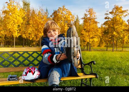 Bildnis eines Knaben, die immer bereit für skating sitzen auf der Bank im Herbst park - Stockfoto