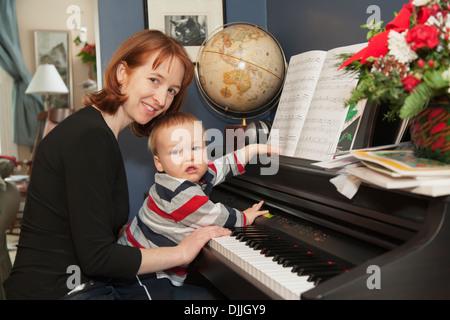 Ein 15 Monate Alter jungen sitzt auf seiner Mutter Schoß, während sie ihn In ihrem Haus ein elektronisches Klavier - Stockfoto