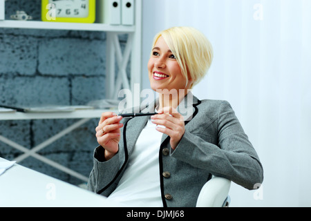 Entspannende glücklich Geschäftsfrau auf ihrem Arbeitsplatz im Büro - Stockfoto