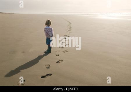 Junges Mädchen am Strand Spuren geht in die Ferne schauen - Stockfoto