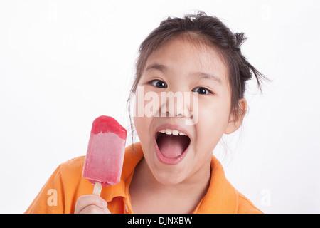 Kleine Asiatin zufrieden mit dem Essen Eis isoliert - Stockfoto