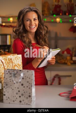 Glückliche junge Frau mit Einkaufstüten Check-Liste der Geschenke in Weihnachten eingerichtet Küche - Stockfoto