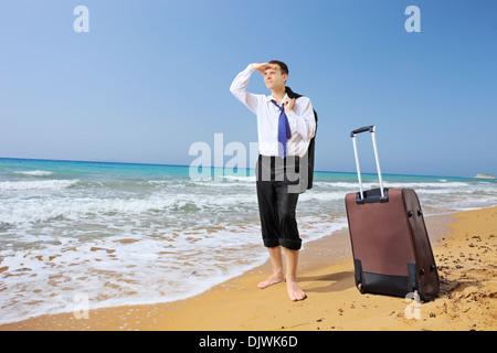 In voller Länge Portrait eines verlorenen Geschäftsmann mit seinem Gepäck auf der Suche nach Möglichkeit an einem - Stockfoto