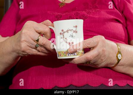 ältere Frau mit einer Tasse - Stockfoto