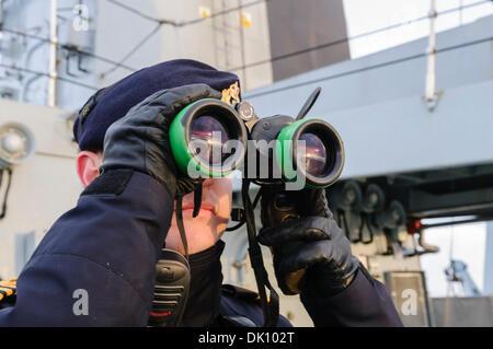 Belfast, Nordirland. 30. November 2013 - blickt Royal Navy Matrose auf das Meer mit dem Fernglas. Bildnachweis: - Stockfoto