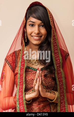 Porträt einer schönen indischen Frau gekleidet in traditioneller Kleidung, Hand in Hand im Namaste-Geste. - Stockfoto