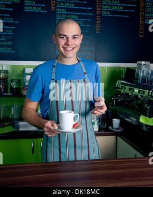 Junge Barkeeper lächelnd und Tasse Kaffee halten. - Stockfoto