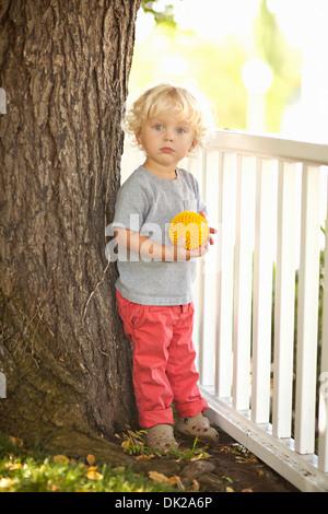 Porträt von blonde Kleinkind Jungen mit dem lockigen Haar mit gelben Ball durch Baumstamm und Zaun im Hinterhof - Stockfoto