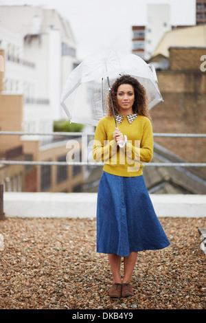 Weibliche Büroangestellte auf Dach hält Regenschirm - Stockfoto