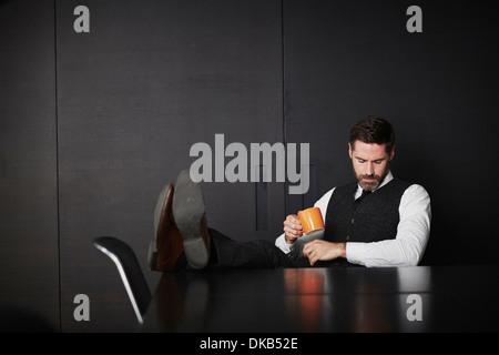 Geschäftsmann mit Füße hoch halten Kaffee - Stockfoto