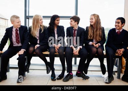 Gruppe von Jugendlichen Schüler sitzen im Korridor - Stockfoto