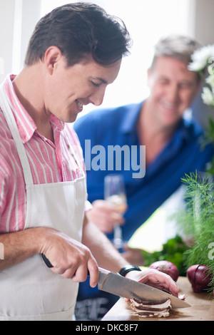 Reifer Mann hacken roten Zwiebel, Mann im Hintergrund - Stockfoto
