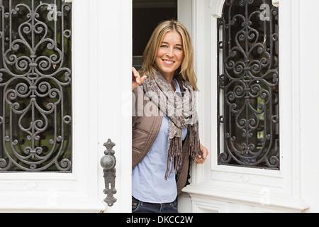 Mitte Erwachsene Frau vor Türöffnung - Stockfoto