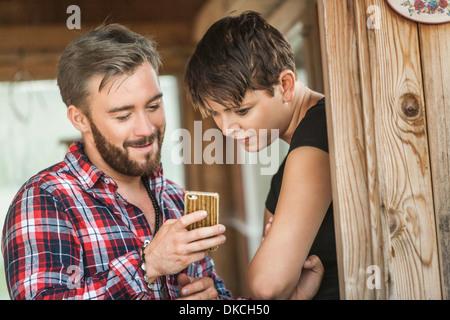 Junges Paar Blick auf Handy - Stockfoto