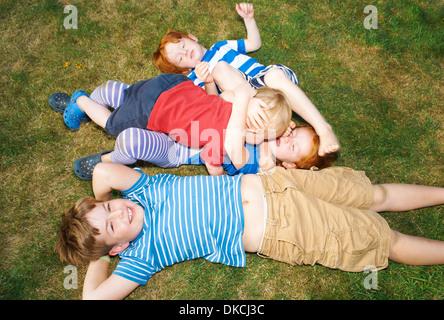 Drei Brüder und Schwester liegen auf dem Rasen im Garten - Stockfoto