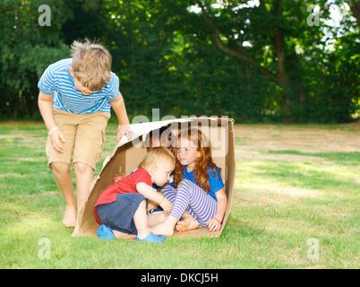 Geschwister im Karton im Garten versteckt - Stockfoto