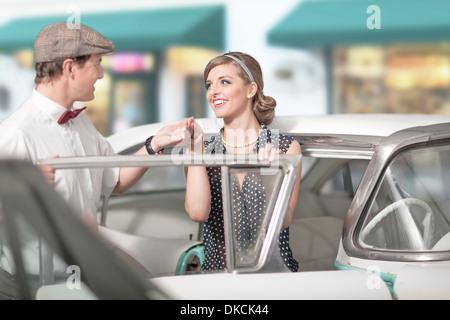Mann hilft Frau aus Oldtimer - Stockfoto