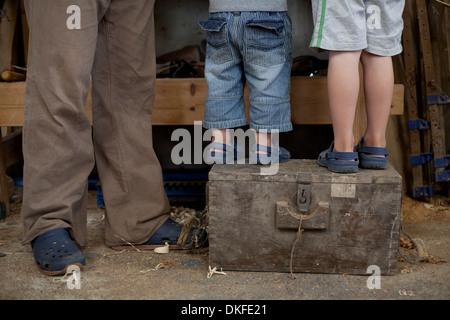 Vater mit Söhnen auf Werkzeugkasten in Boot Werkstatt stehen - Stockfoto