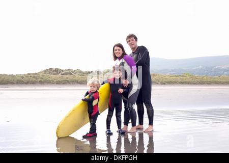 Familie mit zwei Jungs und Surfbrett am Strand - Stockfoto