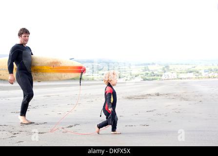 Vater mit Surfbrett mit Sohn am Strand - Stockfoto