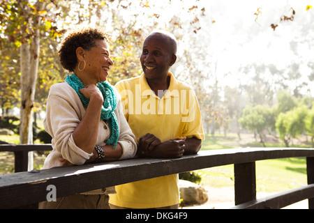 Älteres paar stützte sich auf Fußgängerbrücke im park - Stockfoto