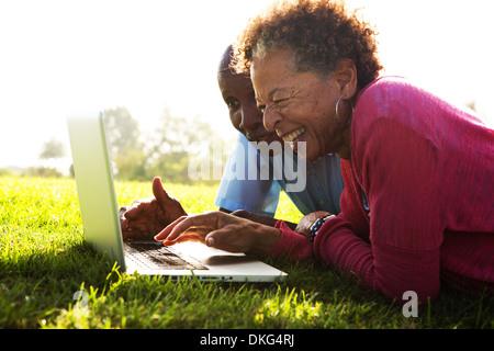 Älteres paar liegen im Park mit laptop - Stockfoto