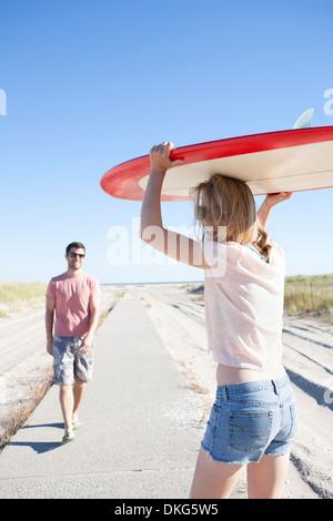 Paar mit Surfbrett auf Küstenweg, Breezy Point, Queens, New York, USA - Stockfoto