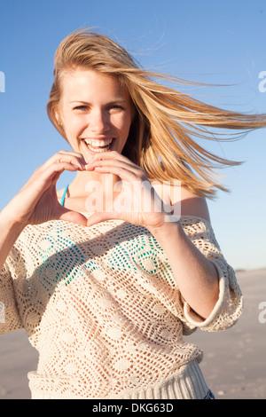 Lächelnde Frau machen Herzschild mit Händen, Breezy Point, Queens, New York, USA - Stockfoto