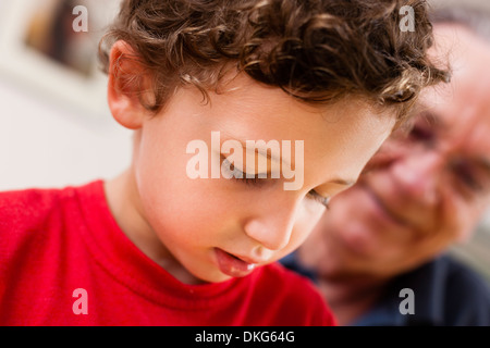 Nahaufnahme eines kleinen Jungen und Großvater im Wohnzimmer - Stockfoto