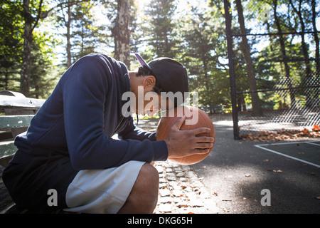 Junger Mann sitzt auf der Parkbank ruhen Kopf auf basketball - Stockfoto