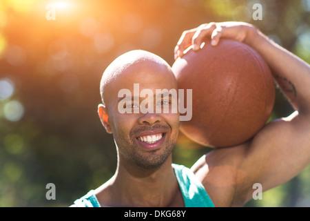 Porträt des jungen Mannes hält basketball - Stockfoto