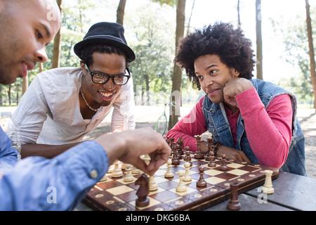 Drei junge Männer spielen Schach im park