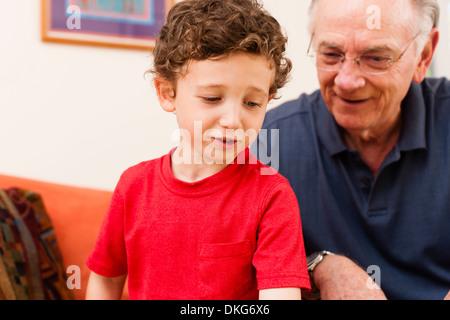 Junge und Großvater im Wohnzimmer - Stockfoto