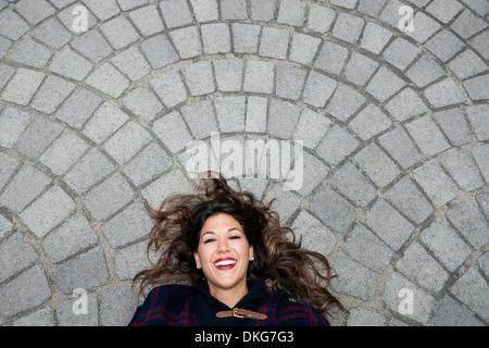 Mitte Erwachsene Frau liegend auf Asphalt, Blick in die Kamera - Stockfoto