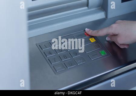 Frau eine Buchungsart auf der Bank ATM, drücken die rote Taste mit dem Finger auswählen - Stockfoto