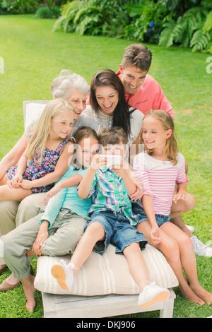 Familie mit Handy zusammen im Hinterhof - Stockfoto