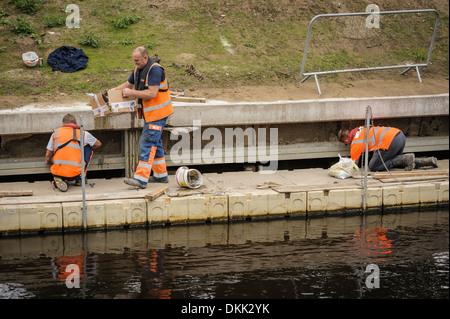 Drei Arbeiter arbeiten Männer bei der Arbeit tragen orange hi-Vis Westen, Inspektion oder Wartung eine konkrete - Stockfoto